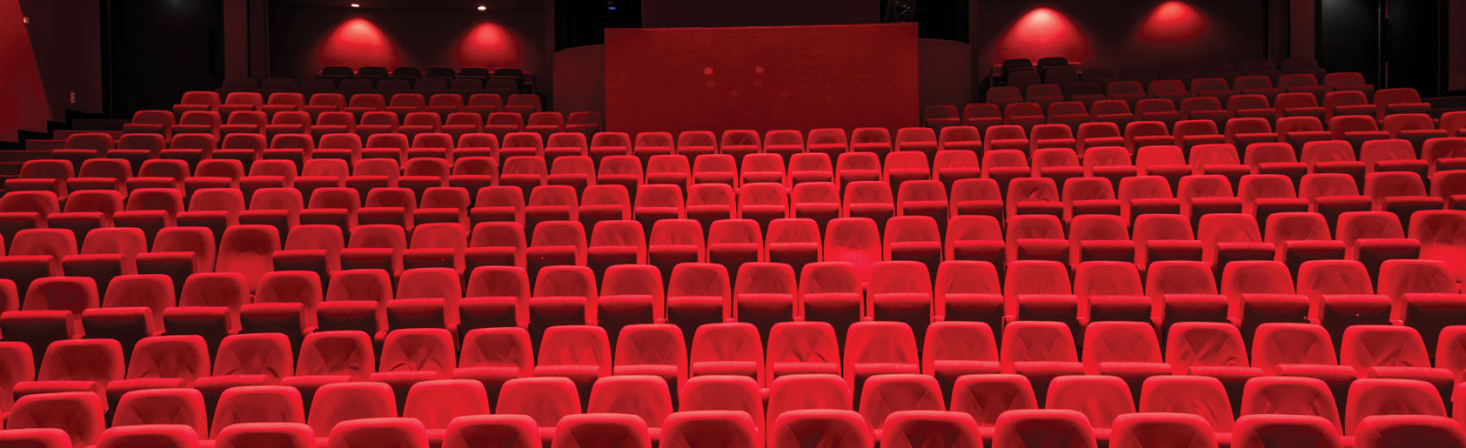 Empty red seats in a large theater.